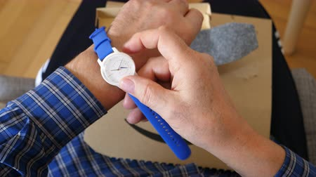 amazon prime : Paris, France - Mar 29, 2019: Senior man put on hand after unboxing unpacking latest Withings move activity tracking watch with Unsurpassed battery life and Infinite possibilities for customize blue strap band