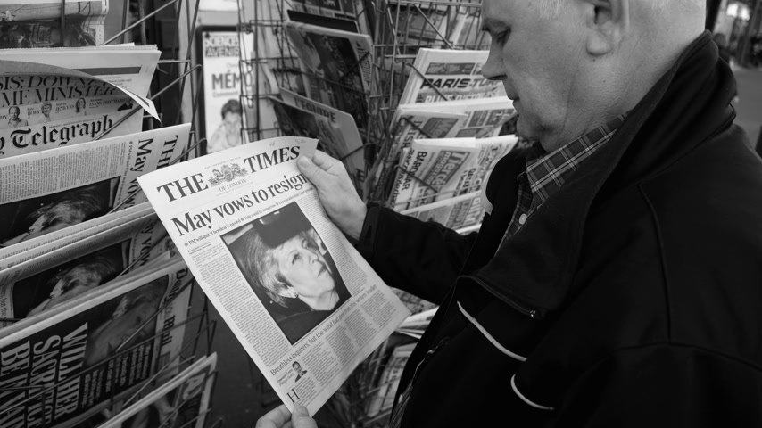 latest : Paris, France - 29 Mar 2019: Newspaper stand kiosk selling press with senior male hand buying latest The Times UK press featuring Theresa may PM on front cover black and white