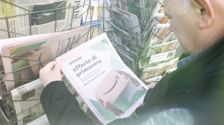 sütunlar : Paris, France - 29 Mar 2019: Sunlight flare over newspaper stand kiosk selling press with senior male hand buying latest Italian press featuring Amazon Oferta di Primavera spring offer on front cover cinematic flare