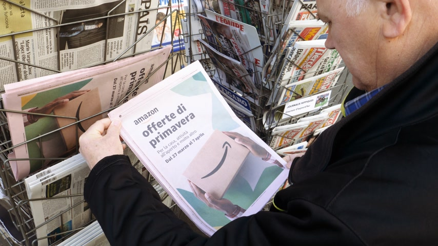 daily : Paris, France - 29 Mar 2019: Newspaper stand kiosk selling press with senior male hand buying latest Italian press featuring Amazon Oferta di Primavera spring offer on front cover Stock Footage