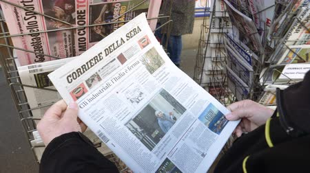 buy newspaper : Paris, France - 29 Mar 2019: POV Newspaper stand kiosk selling press with senior male hand buying latest Italian Corriere Della sera featuring Theresa May on front cover Brexit