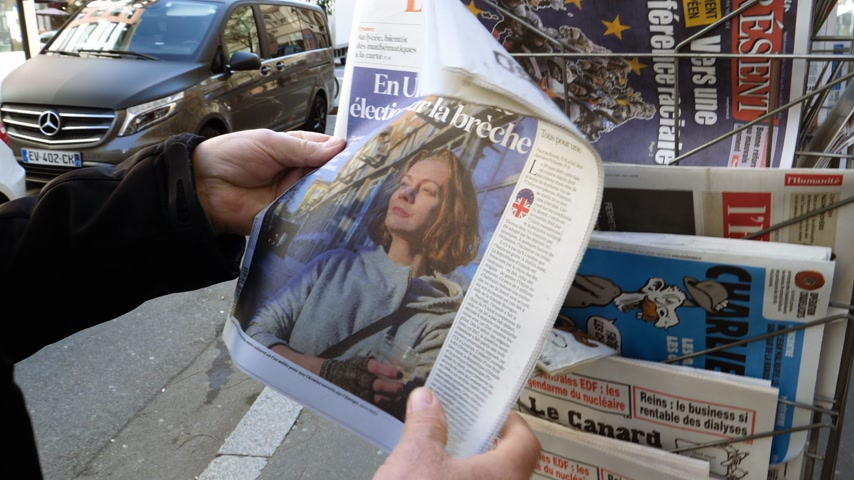 buy newspaper : Paris, France - 29 Mar 2019: Newspaper stand kiosk selling press with senior male hand buying latest La Croix featuring news about Presidential Elections in Ukraine on front cover