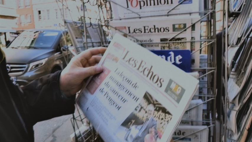 buy newspaper : Paris, France - 29 Mar 2019: Newspaper stand kiosk selling press with senior male hand buying latest economical Les Echo featuring news about Peugeot car maker on front cover VHS vintage tape Stock Footage