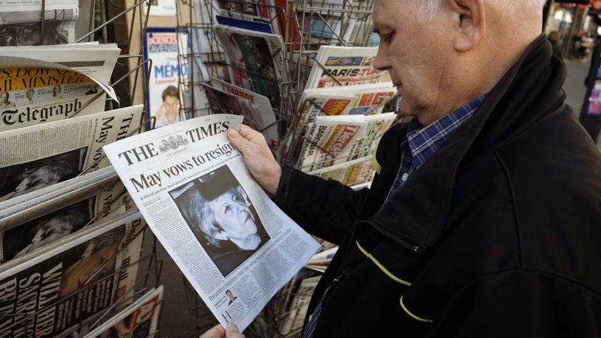 front cover : Paris, France - 29 Mar 2019: Newspaper stand kiosk selling press with curious senior male hand buying latest The Times UK press featuring Theresa may PM on front cover Stock Footage