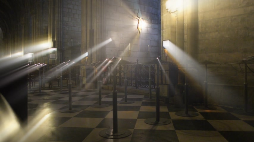 crucified : Iridescent beams rays of warm yellow light coming from Jesus Christs statue crucifixion inside Notre-Dame de Paris cathedral in France
