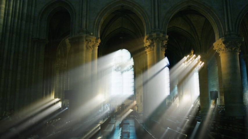 stained glass : Paris, France - Circa 2017: Cinematic rays of light over iridescent beams through windows columns and stained glass windows with rooftop and magnificent chandelier of Notre-Dame de Paris cathedral with visitors tourists people Stock Footage
