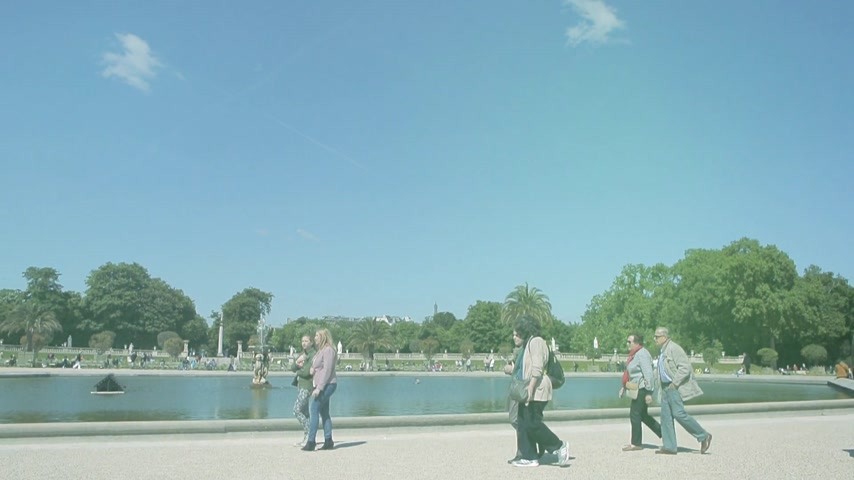 administracja : Paris, France - Circa 2017: Cinematic sunlight flare over people walking in front of Jardin du Luxembourg fountain on a warm day
