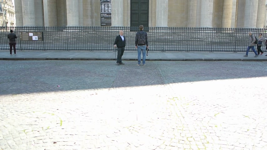 un : Paris, France - Circa 2014: Pedestrians locals and tourists in front of Pantheon Mausoleum in Paris with cinematic sunlight flare - pan over the wide stone facade Stok Video