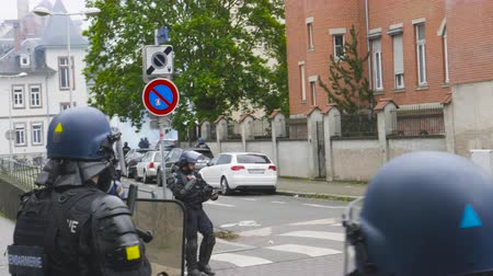 teargas : Strasbourg, France - Apr 28, 2019: French gendarmes police officers intervention with tear gas on rue Daniel Hirtz street during altercations yellow vests waste bin fire