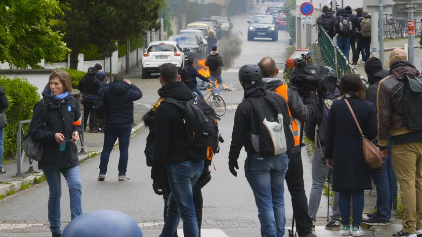 teargas : Strasbourg, France - Apr 28, 2019: Rear view French journalists reporting as gendarmes police officers intervention with tear gas on rue Daniel Hirtz street during altercations yellow vests waste bin fire