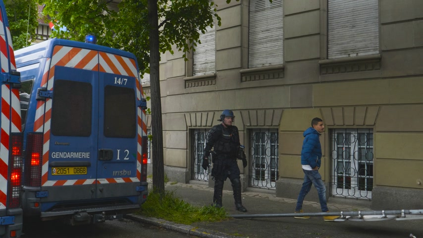 gösterici : Strasbourg, France - Apr 28, 2019: Handheld live reporting video of Police officer securing zone during Yellow Vest on Rue Rene Schickele street after altercations