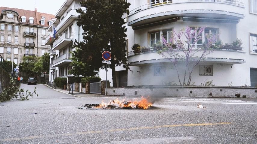 champs elysee : Strasbourg, France - Apr 28, 2019: Cinematic waste garbage bin on fire left by Yellow vests gilets jaunes after demonstration on Rue de la Schiffmatt near European Institutions slow motion Stock Footage