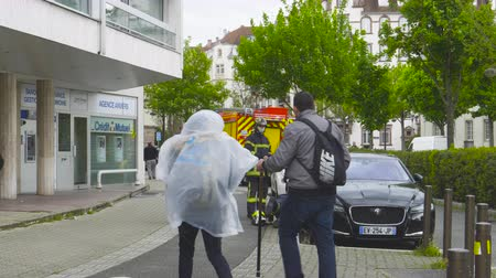 pompiers : Strasbourg, France - Apr 28, 2019: Firefighters sapeurs pompiers talking helping woman to get object fall under a luxury Jaguar car