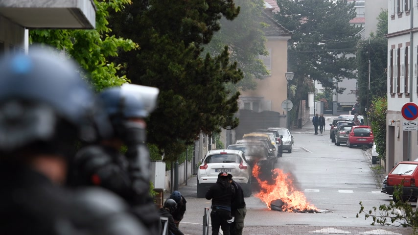reportaje : Strasbourg, France - Apr 28, 2019: Defocused view of Police officer securing street with waste bin in fire caused by Yellow Vest on Rue Rene Schickele street after altercations