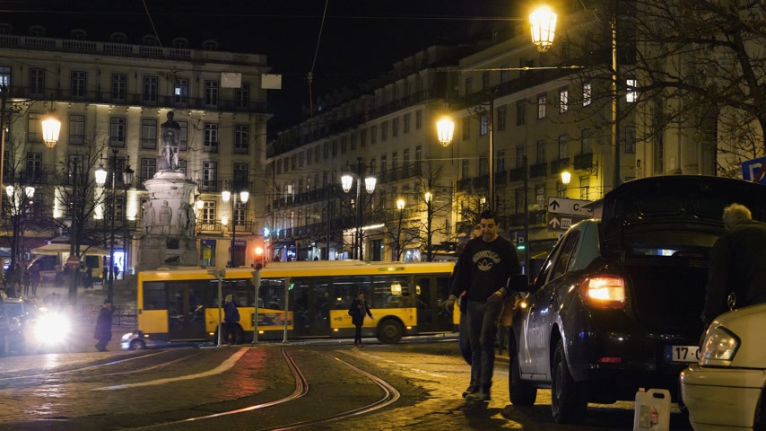 lizbona : Lisbon, Portugal - Circa 2019: Young couple walking on the praca Luis de Camoes square at night with taxis cars, pedestrians, people walking discovering the city