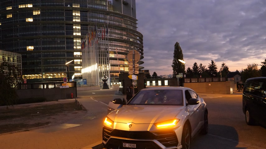 milliomos : Strasbourg, France - Circa 2019: Couple traveling in luxury Lamborghini Urus SUV taking photos of the European Parliament building at night in Strasbourg with al EU waving flags in background