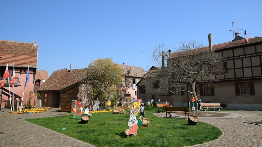 half timbered : Bergheim, France - 19 Apr 2019: Kids playing near water fountain with multiple Easter decorations on the lawn Stock Footage