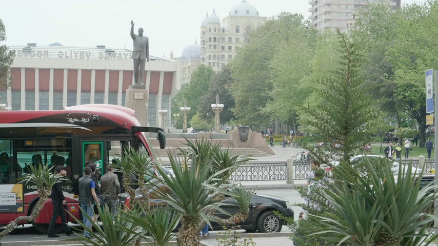 prezident : Baku, Azerbaijan - Circa 2019: Cinematic Heydar Aliyev Palace with saluting statue in memory of Azerbaijani President Heydar Aliyev with people entering bus in red public transportation bus