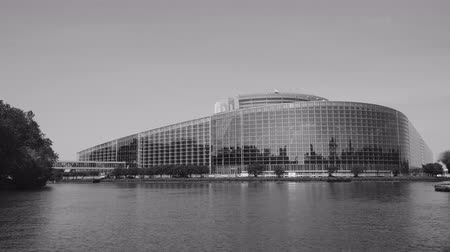 all european flags : Clear wide facade of European Parliament headquarter in Strasbourg a day before 2019 European Parliament election - clear sky and calm Ill river water - black and white
