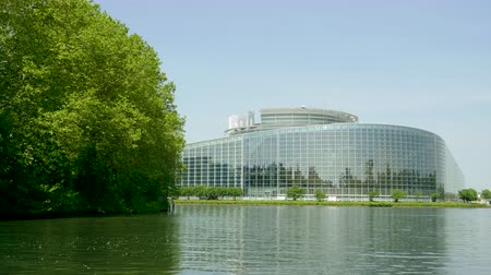 all european flags : Clear wide facade of European Parliament headquarter in Strasbourg a day before 2019 European Parliament election - clear blue sky and calm Ill river water