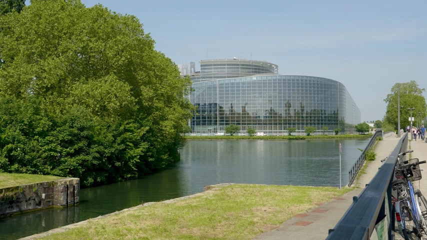 parlamento : Strasbourg, France - May 23, 2019: Group of people walking on the bridge with European Parliament headquarter building in background Stok Video