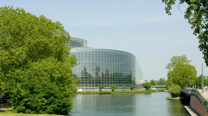all european flags : Wide facade of European Parliament headquarter in Strasbourg a day before 2019 European Parliament election - clear blue sky and calm Ill river water Stock Footage