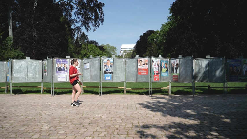 migrants : Strasbourg, France - May 23, 2019: Posters in green sunny park for 2019 European Parliament election featuring French politicians and female runner in front checking phone - slow motion