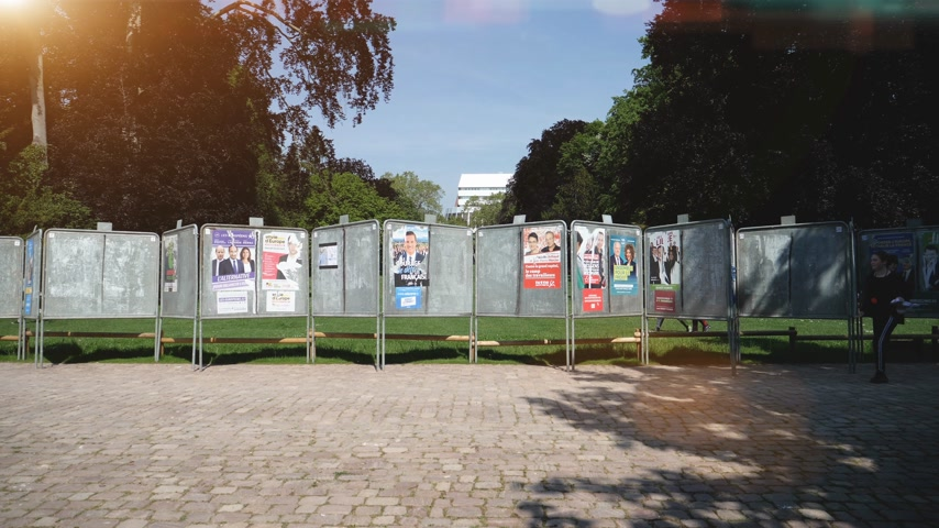 migrants : Strasbourg, France - May 23, 2019: Posters in green sunny park for 2019 European Parliament election featuring French politicians and female runner in front - slow motion Stock Footage