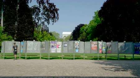 migrants : Strasbourg, France - May 23, 2019: Posters in green sunny park for 2019 European Parliament election featuring French politicians and male runner looking at candidates