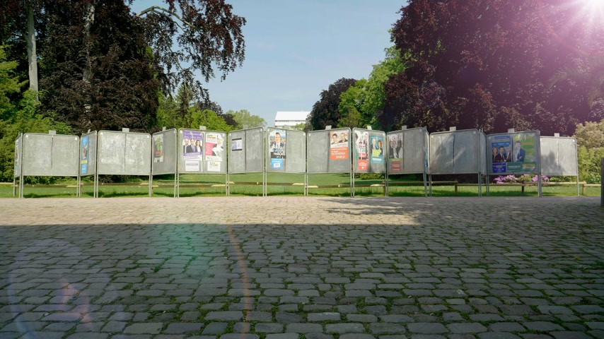 migrants : Strasbourg, France - May 23, 2019: Sunlight cinematic flare over posters in green sunny park for 2019 European Parliament election featuring French politicians candidates Stock Footage