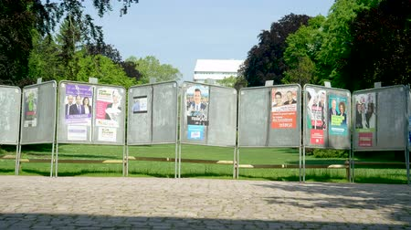 migrants : Strasbourg, France - May 23, 2019: Sunlight cinematic flare over posters in green sunny park for 2019 European Parliament election featuring French politicians candidates - establishing shot