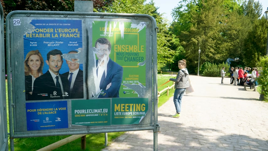 migrants : Strasbourg, France - May 23, 2019: Posters green sunny park for 2019 European Parliament election featuring French politicians from Les Republicains and Ecologist party - young kids in background