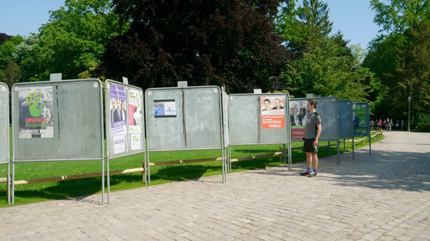 migrants : Strasbourg, France - May 23, 2019: Side view of posters in green sunny park for 2019 European Parliament election featuring French politicians and male runner looking at candidates Stock Footage