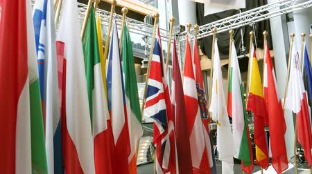 all european flags : Tilt up pto all European Union members flags in the media room pole of European Parliament headquarter in Strasbourg, France Stock Footage