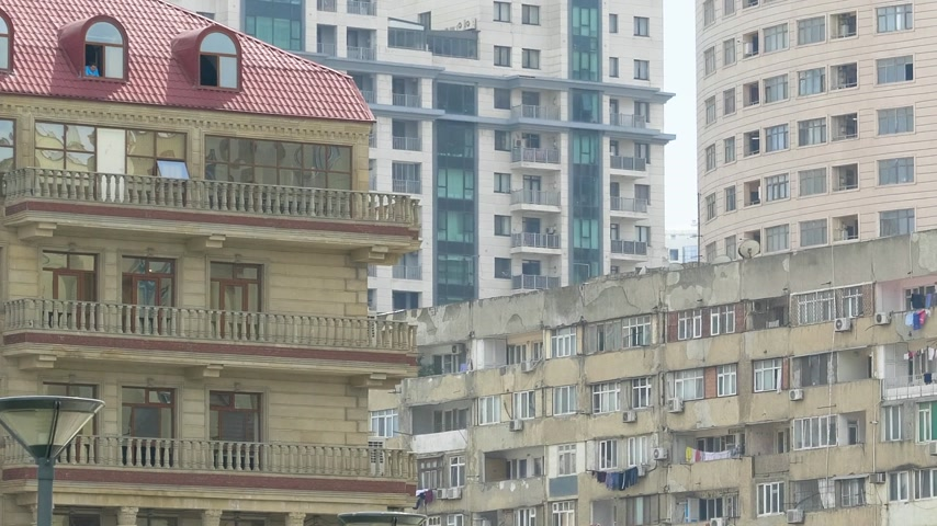 socialismo : Pan over soviet architecture and modern Azerbaijani apartment building - covered balconies and lots if air conditioning units on the balconies - real estate investment in Baku