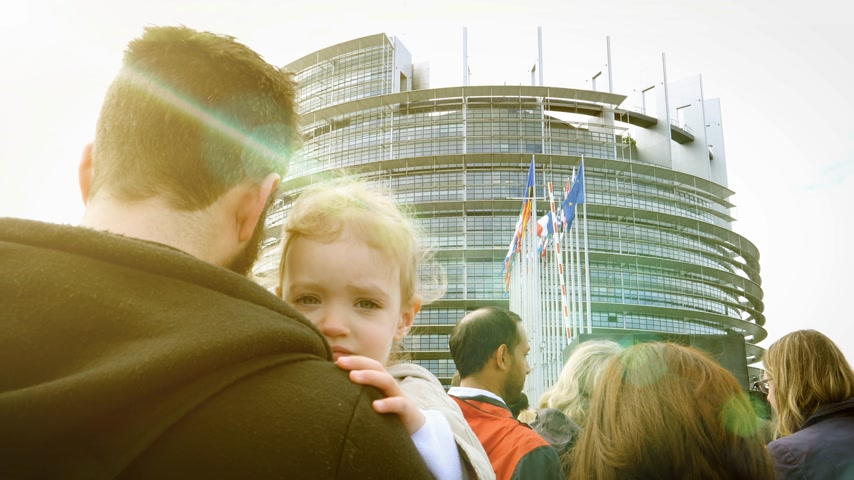 all european flags : Strasbourg, France - Circa 2018: Rear view of father holding young girl waiting in queue at the European Parliament during Open Days for all citizens interested to know how Parliament works - cinematic flare Stock Footage