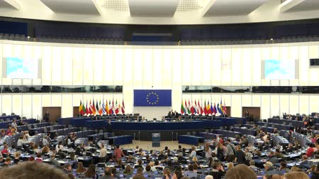 helyettes : Strasbourg, France - Circa 2018: People inside hemicycle of European Parliament headquarter in Strasbourg with all Eu Members flags on the tribune and explanation about how parliament works Stock mozgókép