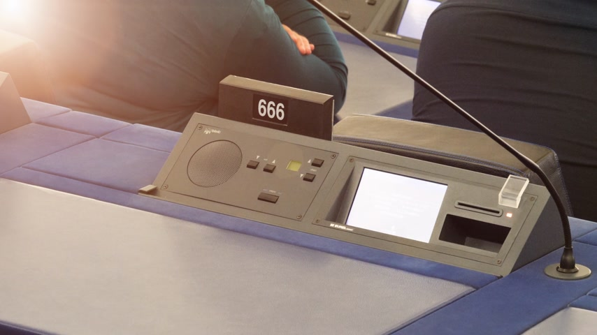 helyettes : Strasbourg, France - Circa 2018: Modern Simultaneous Interpreting translation equipment dashboard with microphone and empty triple six 666 number of European Parliament seat - sunlight flare left corner