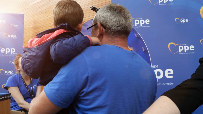 groupe : Strasbourg, France - Circa 2018: European Peoples Party exhibition stand lucky wheel roulette with father and son spinning and winning prize - European Parliament interior during open day