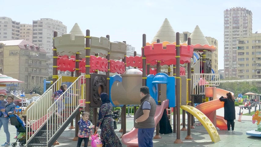 baku : Baku, Azerbaijan - Circa 2019: Kids having fun at the children slide dedicated children zone in Yasamal Parki green oasis in central Baku surrounded with tall apartment real estate buildings