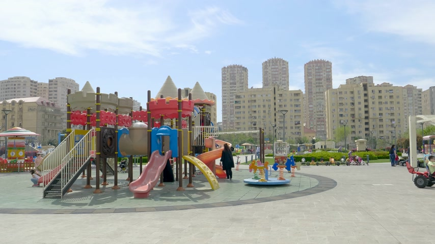 dedicado : Baku, Azerbaijan - Circa 2019: Kids having fun at the dedicated children zone in Yasamal Parki green oasis in central Baku surrounded with tall apartment real estate buildings