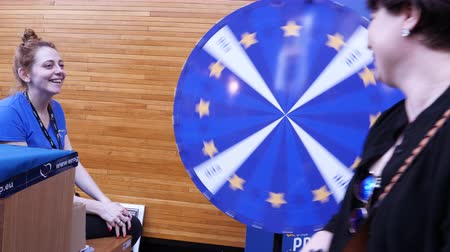 összeg : Strasbourg, France - Circa 2018: European Peoples Party exhibition stand lucky wheel roulette with woman people spinning and winning prize a blue pencil - European Parliament interior during open day Stock mozgókép