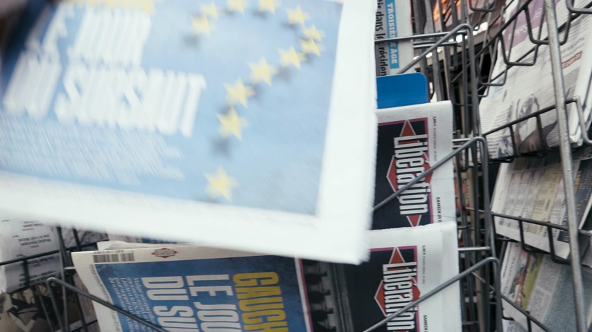 buy newspaper : Strasbourg, France - May 25, 2019: Man hand POV reading at press kiosk Liberation newspaper featuring 2019 European Parliament election predictions a day before the vote