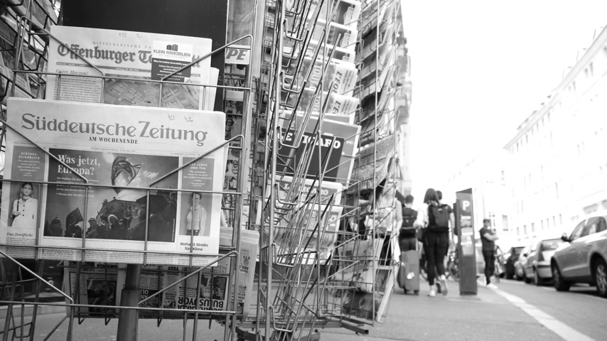 buy newspaper : Strasbourg, France - May 25, 2019: Slow motion press kiosk stand with Sueddeutsche Zeitung German press newspaper featuring 2019 European Parliament election predictions a day before the vote black and white Stock Footage