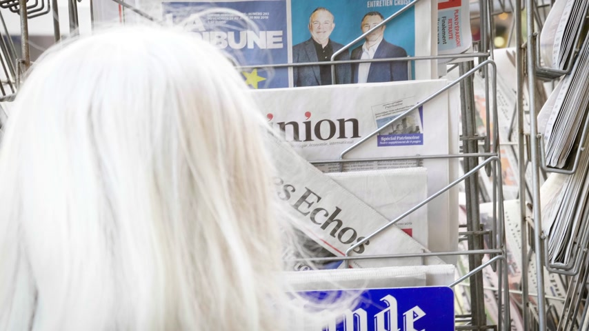buy newspaper : Strasbourg, France - May 25, 2019: Woman buying at press kiosk Les Echos newspaper featuring 2019 European Parliament election predictions a day before the vote