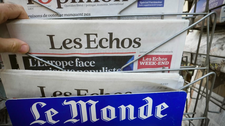 buy newspaper : Strasbourg, France - May 25, 2019: Man hand POV reading at press kiosk Les Echos newspaper featuring 2019 European Parliament election predictions a day before the vote
