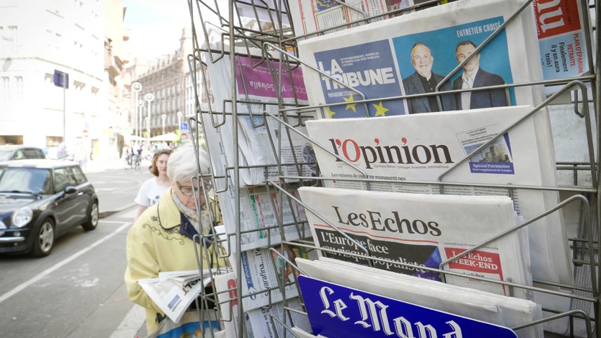 latest : Strasbourg, France - May 25, 2019: French press kiosk multiple newspaper featuring 2019 European Parliament election predictions a day before the vote senior woman reading German press