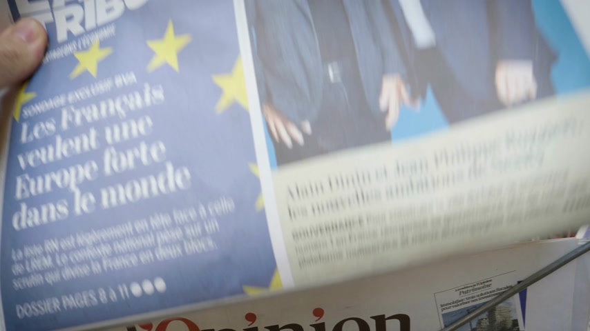 buy newspaper : Strasbourg, France - May 25, 2019: Man hand POV reading at press kiosk La Tribune newspaper featuring 2019 European Parliament election predictions a day before the vote