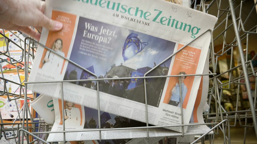 latest : Strasbourg, France - May 25, 2019: Man hand POV reading at press kiosk Sueddeutsche Zeitung newspaper featuring 2019 European Parliament election predictions a day before the vote