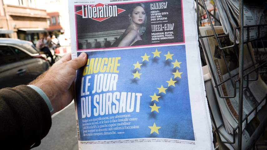 buy newspaper : Strasbourg, France - May 25, 2019: Man hand POV reading at press kiosk newspaper featuring 2019 European Parliament election predictions a day before the vote Left wing a surprise title Stock Footage